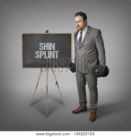 Shin splint text on blackboard with businesssman holding weights