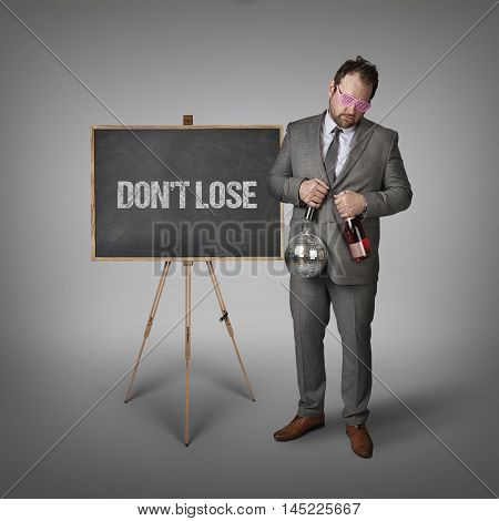 Dont lose text on blackboard with businessman and key