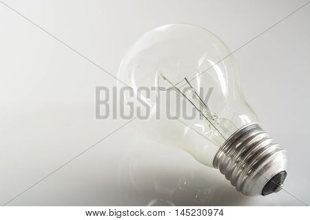 incandescent bulb resting on a glossy white floor
