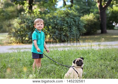 Little boy with his pug dog in a park
