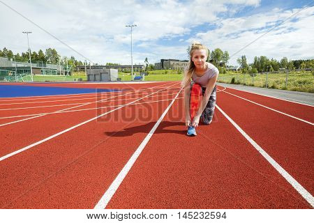 Portrait of sporty determined woman tying shoelace on running tracks