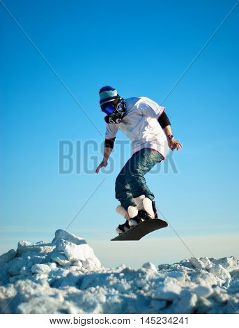 Snowboarder making jump against the clear blue sky