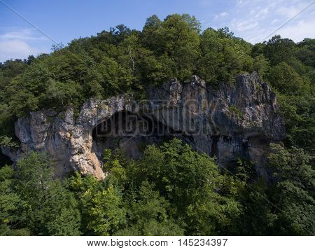 The Cave Entrance On The Side Of A Mountain Covered With Forest.
