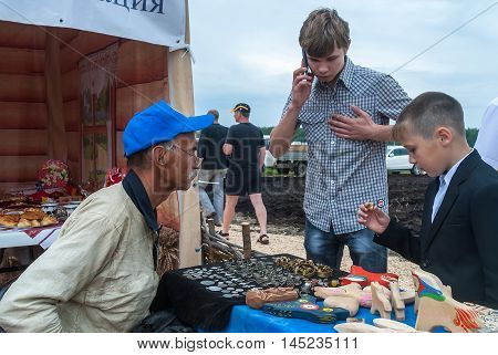 Tyumen, Russia - June 24, 2016: The 5th open championship of Russia on a plowed land. Man numismatist shows his collection of coin