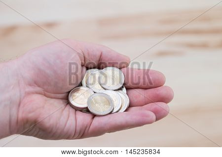 two euro coins in hand. close-up to money