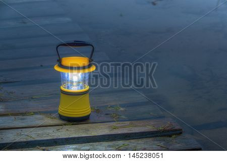 Night view of luminous hand lantern standing on the pier in the lake