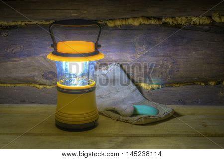 Luminous hand lantern standing on the shelves near mitten and soap