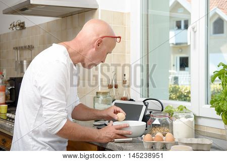 a senior man cooking in the kitchen at home with tablet