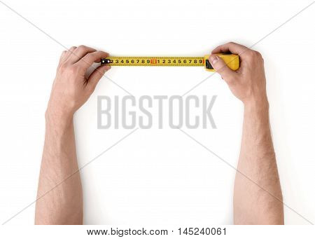 Close-up view of man's hands measuring something with tape-measure isolated on white background. Building and repairing. Handyman. DIY concept.