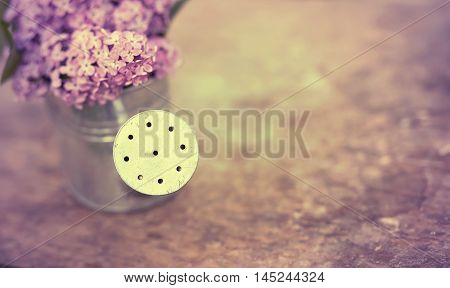 Watering can with lilac flower in spring - gardening concept
