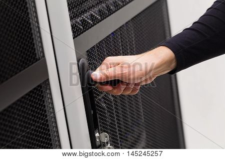 It engineer or consultant opens door to a server rack in data rack. Shot in enterprise datacenter.