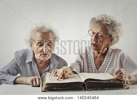 Elderly ladies reading an old book