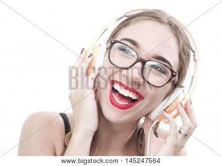 Woman with headphones listening music . Music teenager girl dancing against white.