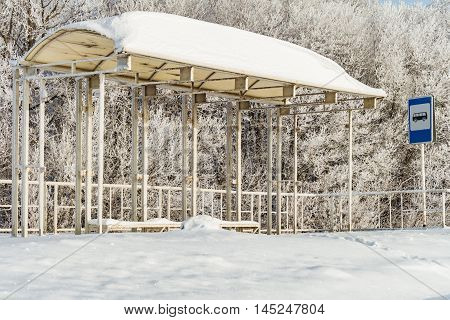 Empty suburban bus stop covered with snow in winter