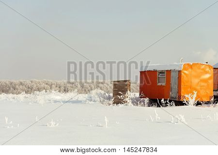 Construction trailer left in the snow. Caravan in winter field. Site container.