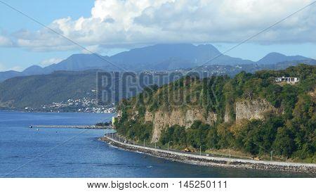 Caribbean coastal highway blue ocean rocky cliff puffy white cloud
