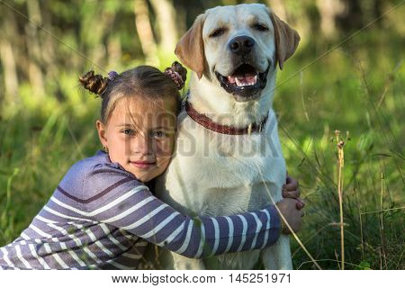 Little girl and her dog outdoors.