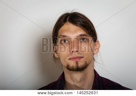 Masculinity concept. Face of young man. Bearded youthful male with long hairs.