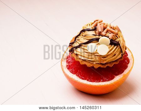 Concept of making choice: healthy low-calorie or unhealthy high-calorie food slimming or fattening. Grapefruit and cake cupcake.