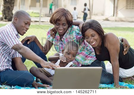 A group of friends and a child looking at a laptop screen . They are all happy.
