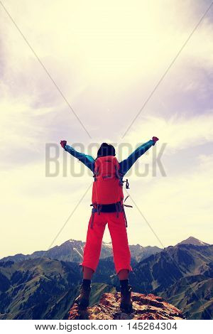 cheering young woman hiker open arms on mountain top