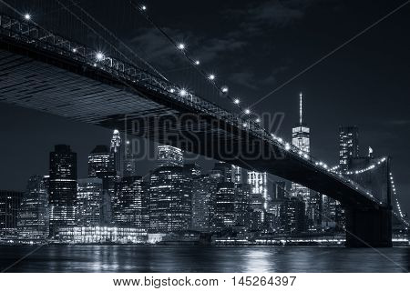 The skyline of downtown Manhattan and the Brooklyn Bridge illuminated at night