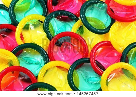 A close up image of a multitude of colored condoms