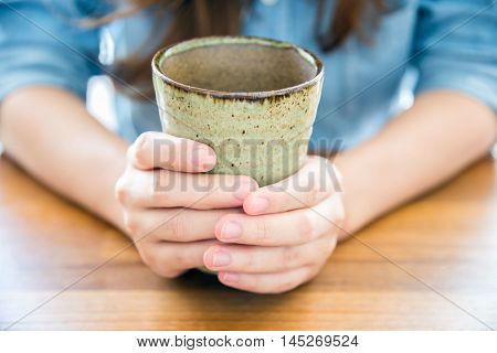 Woman holding ceramic cup in the hands.