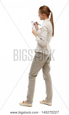 back view of stands woman takes notes in a notebook. girl watching. Isolated over white background. Skinny girl in white denim suit writing in a notebook.