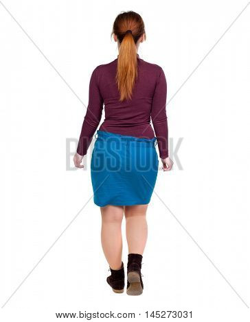 back view of walking woman. beautiful blonde girl in motion. Girl with red hair tied in a pigtail goes deep into the frame.
