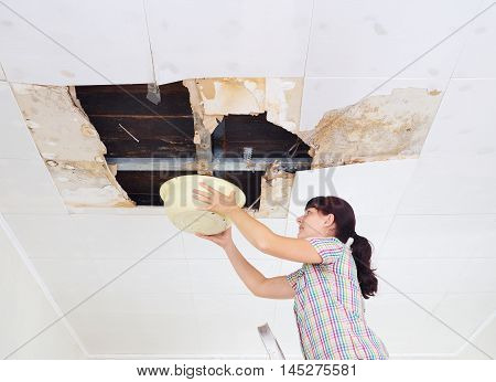 Young Woman Collecting Water In Basin From Ceiling. Ceiling Panels Damaged Huge Hole In Roof From Ra