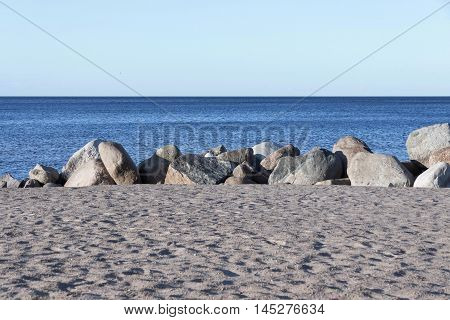 the sandy beach and big stones boulders ashore near water and the line of the horizon over water