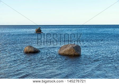three big the isolated stones or boulders on the surface of sea water and the line of the horizon between the sky and water