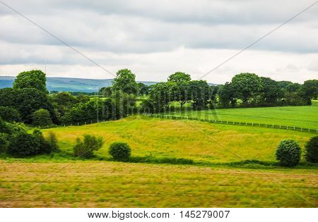 High dynamic range (HDR) English countryside seen from a train near Preston with selective focus on the horizon and motion blur on the foreground