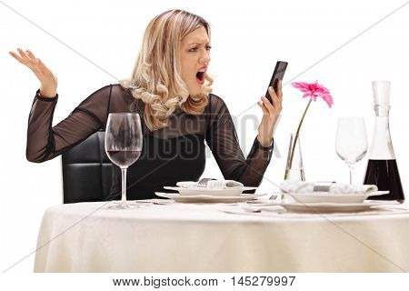 Furious woman sitting at a restaurant table and reading a message on her phone isolated on white background