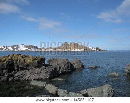 Rock beach and snow mountain background at Antarctica