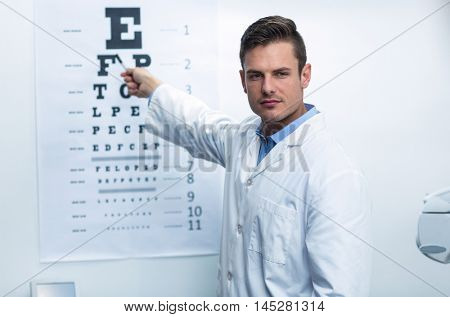 Handsome optometrist pointing at eye chart in ophthalmology clinic