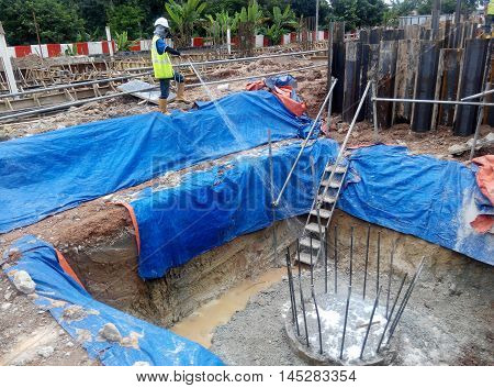 JOHOR, MALAYSIA -JUNE 26, 2015: Construction workers spraying the anti termite chemical treatment to the soil at the construction site.