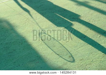 Man's shadow on the ground with badminton racket