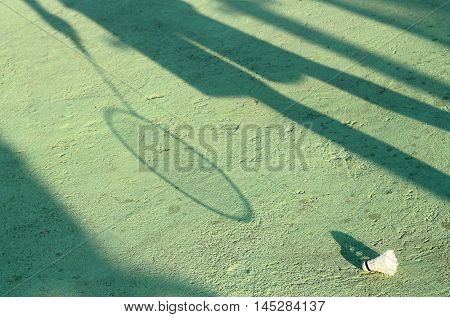 Man's shadow on the ground with badminton racket and old shuttlecock