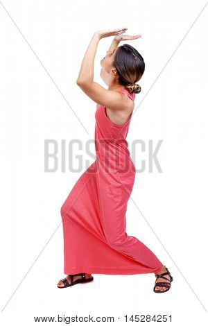 back view of woman protects hands from what is falling from above. A slender woman in a long red dress holds hands something over his head.