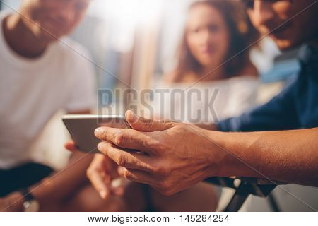 Young Man Showing Mobile Phone To Friends