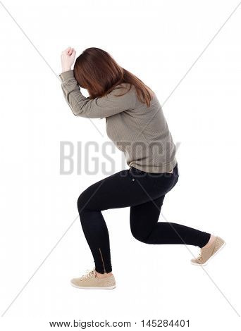 back view of standing young beautiful woman in jeans. backside view of person. Isolated over white background.A girl in a gray sweater in defensive stance.
