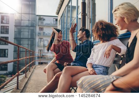 Multiracial group of friends having fun in balcony and giving high five. Young people enjoying in terrace.