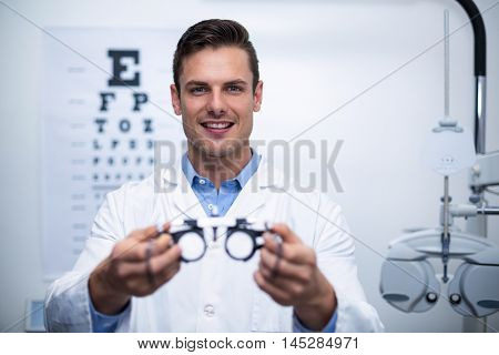 Portrait of smiling optometrist holding messbrille in ophthalmology clinic
