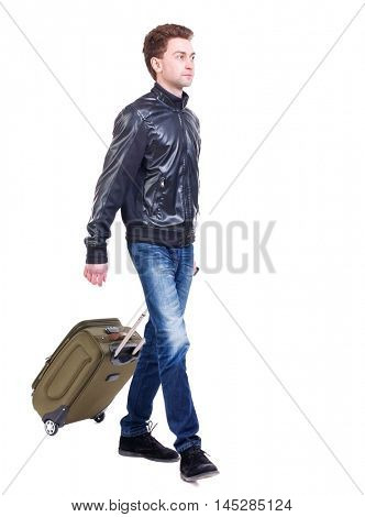 front view of walking man with suitcase. Curly boy rolls a suitcase and looking at the camera in a black leather jacket.