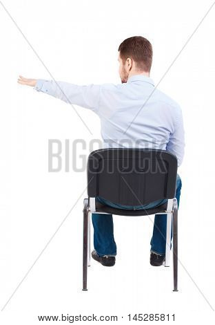back view of young business man sitting on chair and pointing. Bearded businessman in white shirt sitting on the chair arm and points to the side.