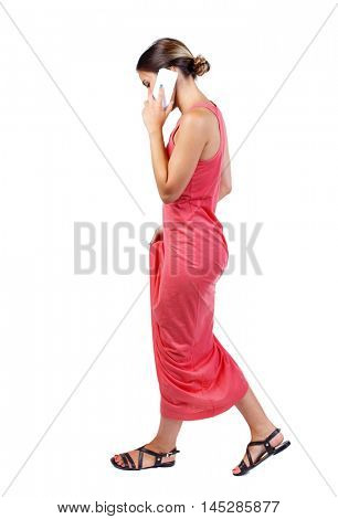 side view of a woman walking with a mobile phone. beautiful girl in motion. backside view of person. slender woman in a long red dress is talking and looking at his feet.