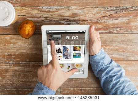 business, blogging, people and technology concept - close up of male hands with internet blog web page on tablet pc computer screen, muffin and coffee cup on wooden table