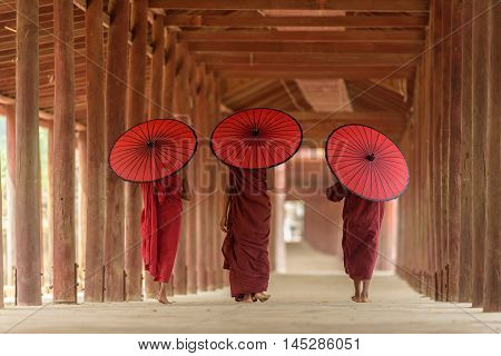 Three Buddhist novices with red umbrella on their shoulder are walking inside pagoda in Mandalay Myanmar
